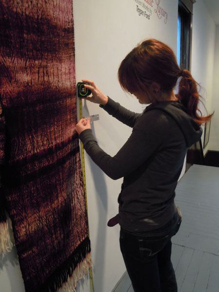 """Myself, hanging my artwork for my Senior Exhibition """"Chromatic Luxury: Woven Works by Tegan Ford"""" in 2011."""