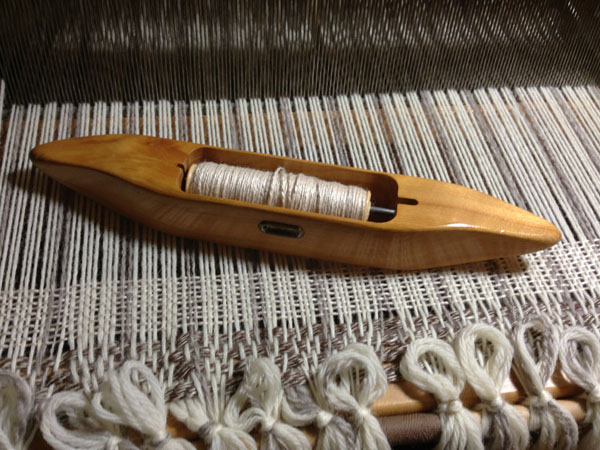A shuttle, containing a bobbin that is loaded up with yarn, which will become weft. The perpendicular lines already in the warp is weft.