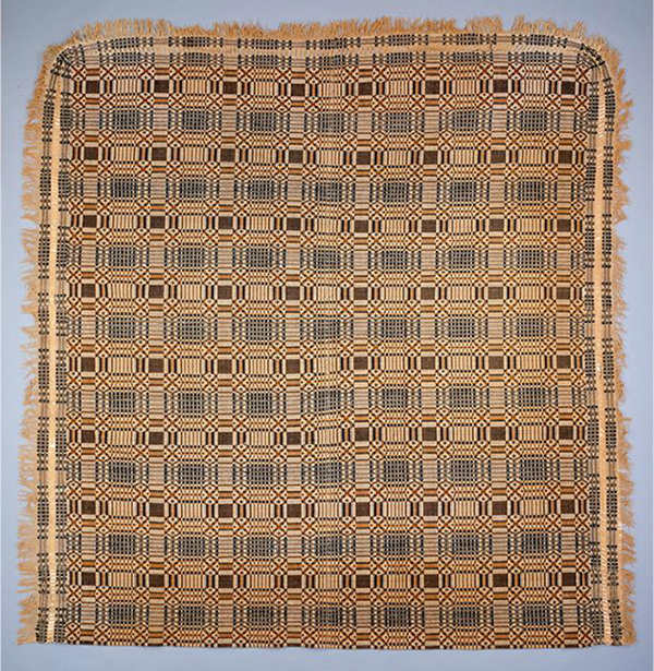 A beautiful overshot coverlet with fringe on three sides.