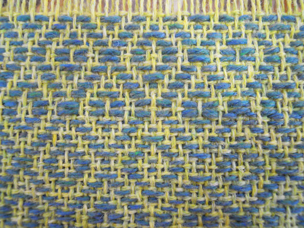 Here is a close up of that change. You can see that instead of being an integral part of the weaving, the pattern weft is just floating over top of the tabby threads.